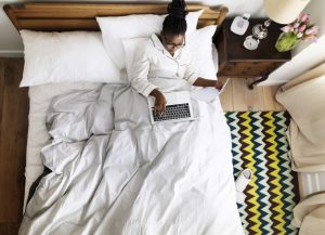 African American business woman on bed working